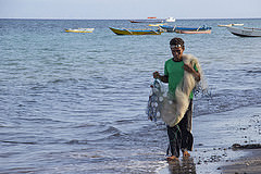 A fisherman carries his net along the share in Atauro, Timor-Leste. Photo by Holly Holmes, 2013